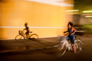 Young boy and his shadow cycle through Hoi An at night