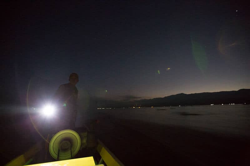 A man drives a boat late at night on Inle lake in Myanmar