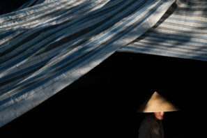 A low key photo of a Vietnamese woman walking under a blue tarp in a market of Vietnam taken during Pics of Asia photography workshop
