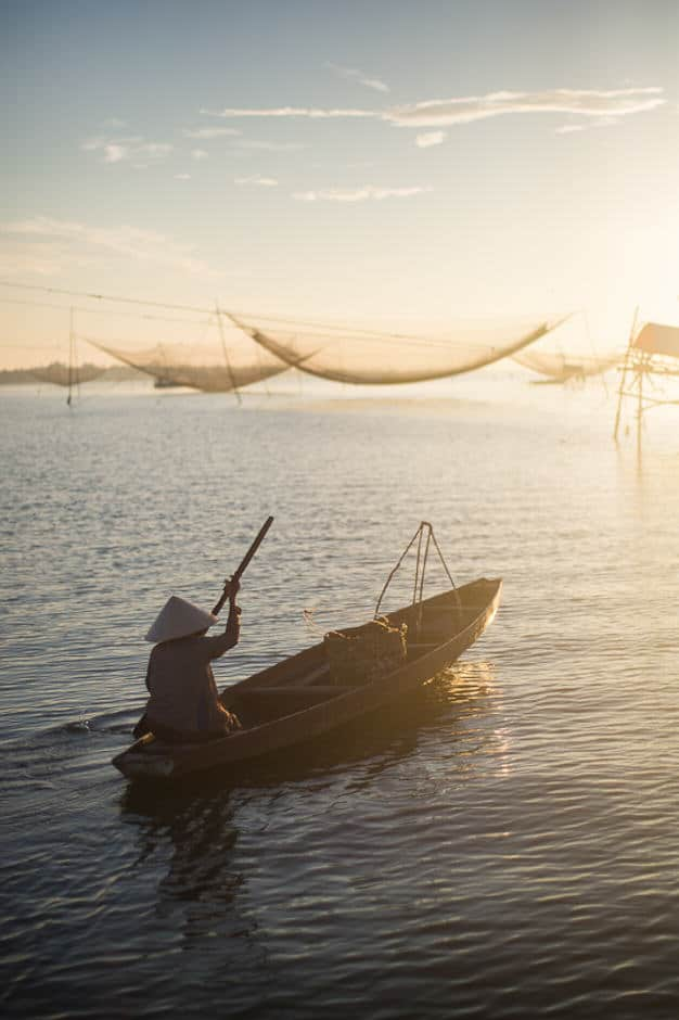 Vietnamese woman on a boat with fishing nets