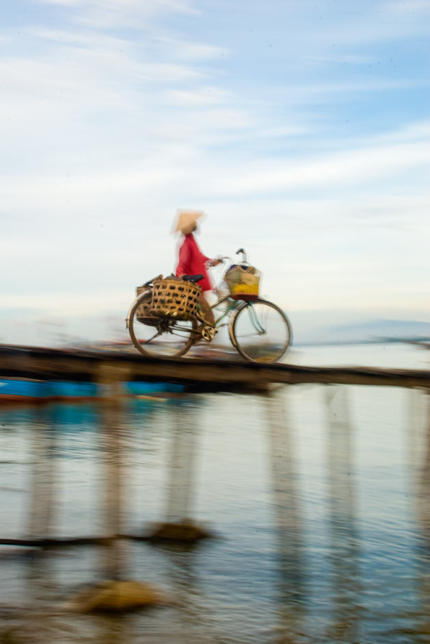 Woman in Vietnam going down a peer with her bicycle