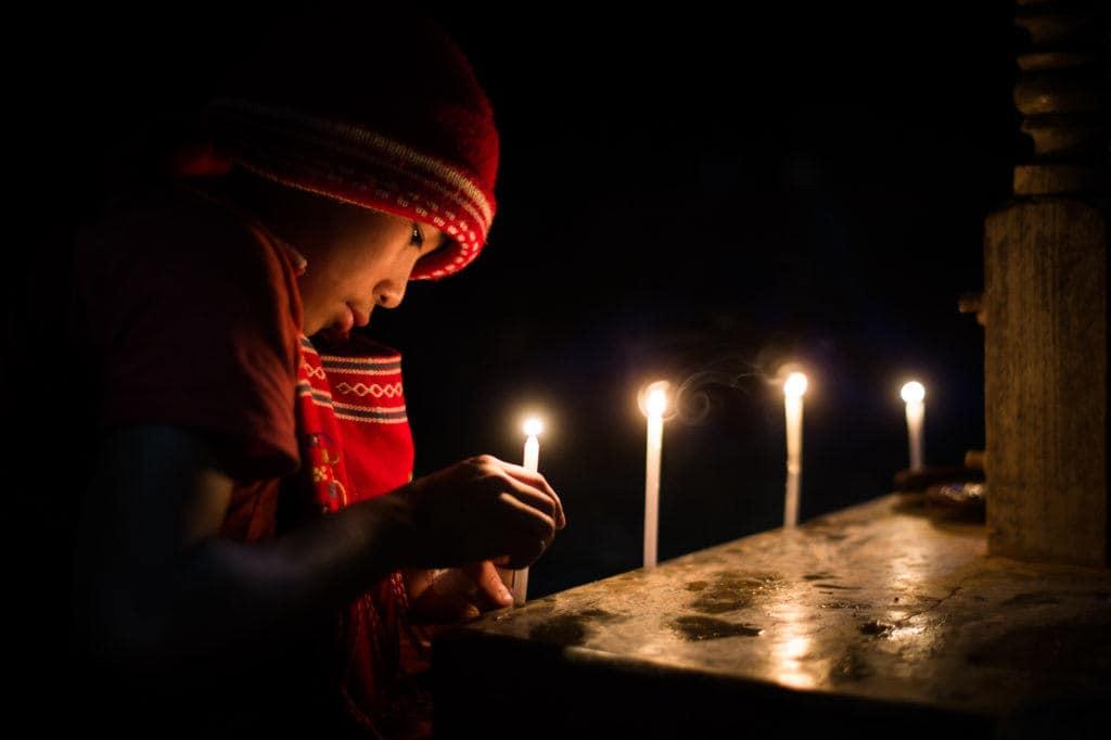 Novice monk in Myanmar lighting candles at night