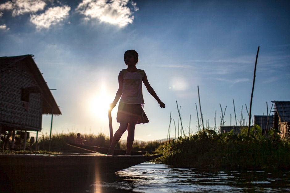 Burmese girl rowing boat on Inle lake