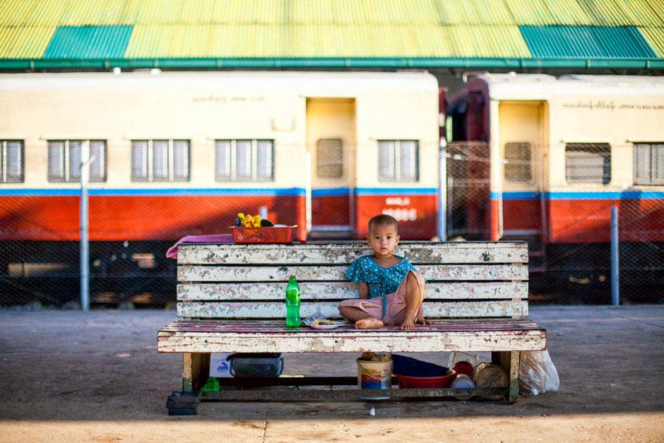 Young girl sitting on a bench in Yangon train station
