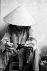 Vietnamese woman rolling a local cigar