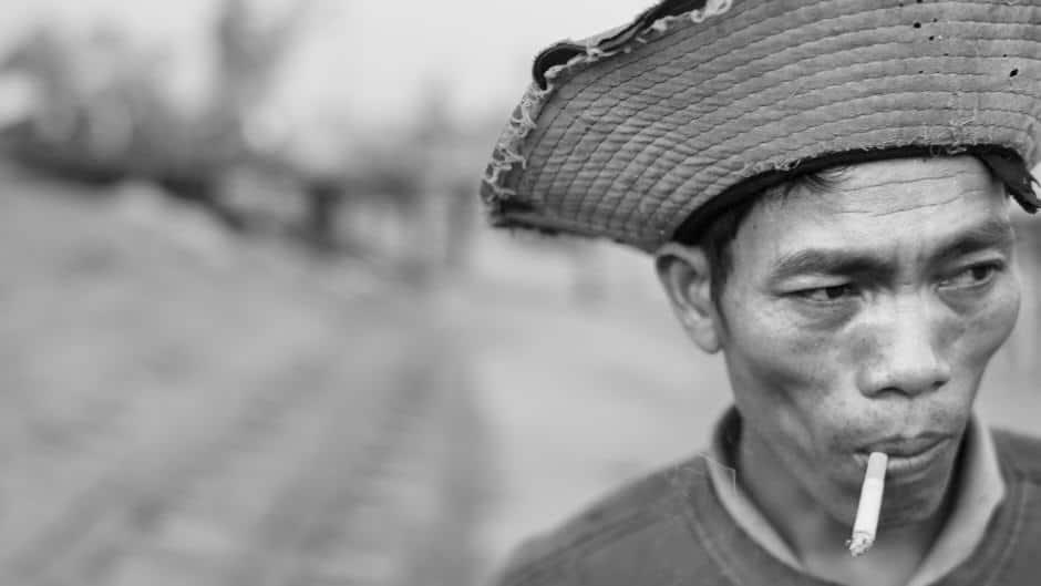 blacm and white portrait of a Vietnamese fisherman smoking a cigarette