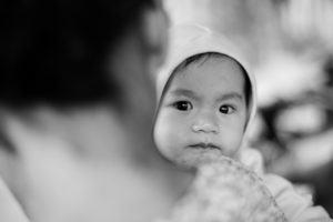 Vietnamese boy hiding behind his older sister