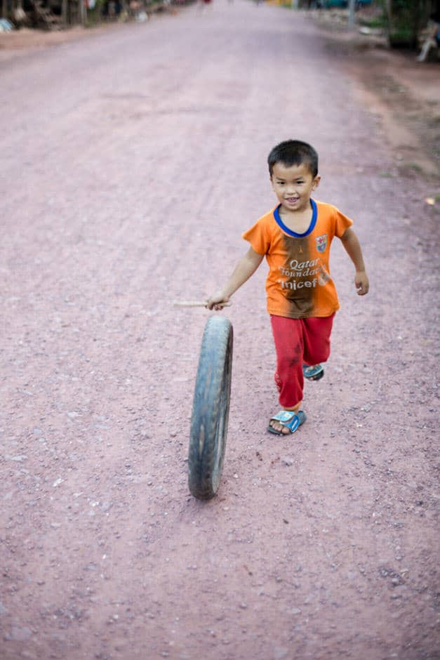 A young Lao boy playing with a tire, Luang Nam Tha.