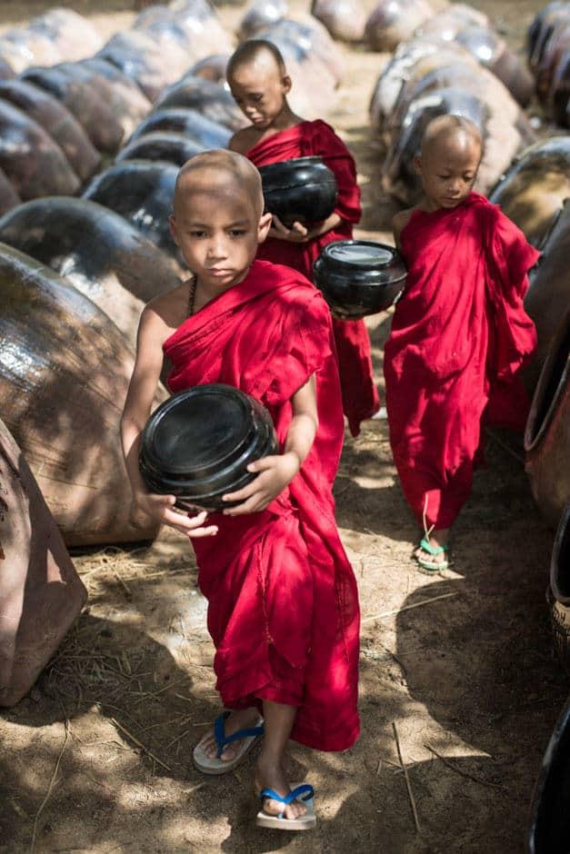 3 Burmese monks walking among big pots in Bagan, Myanmar.