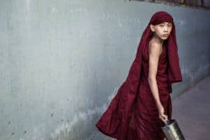 Novice walking in a small alley in Mandalay, Myanmar
