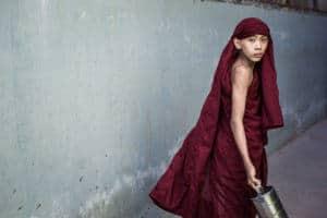 Novice walking in a small alley in Mandalay, Myanmar