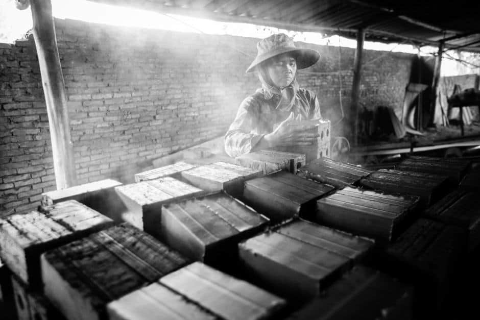 Woman working in a smoking brick factory in Laos