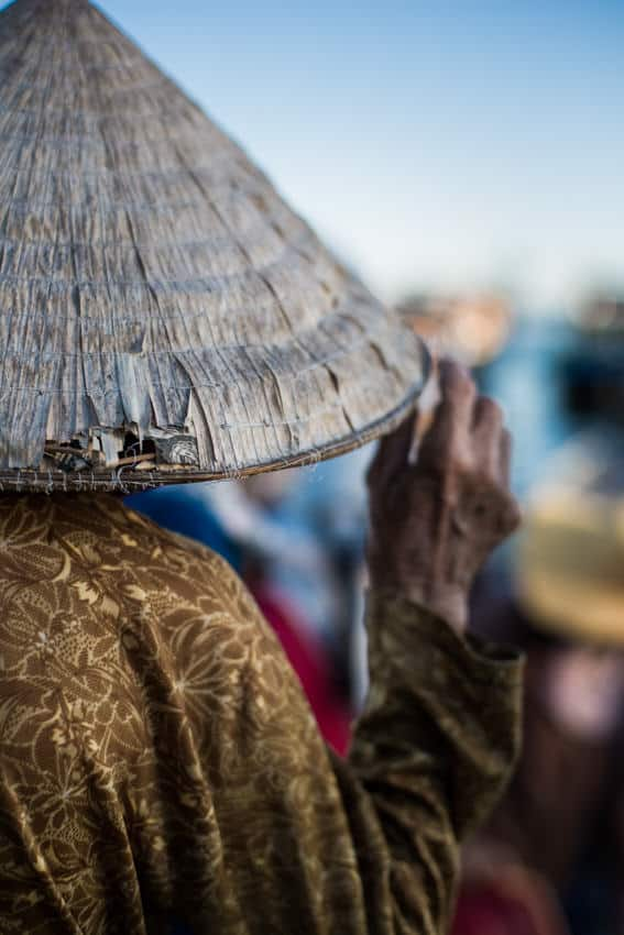 A Vietnamese woman holds her conical hat