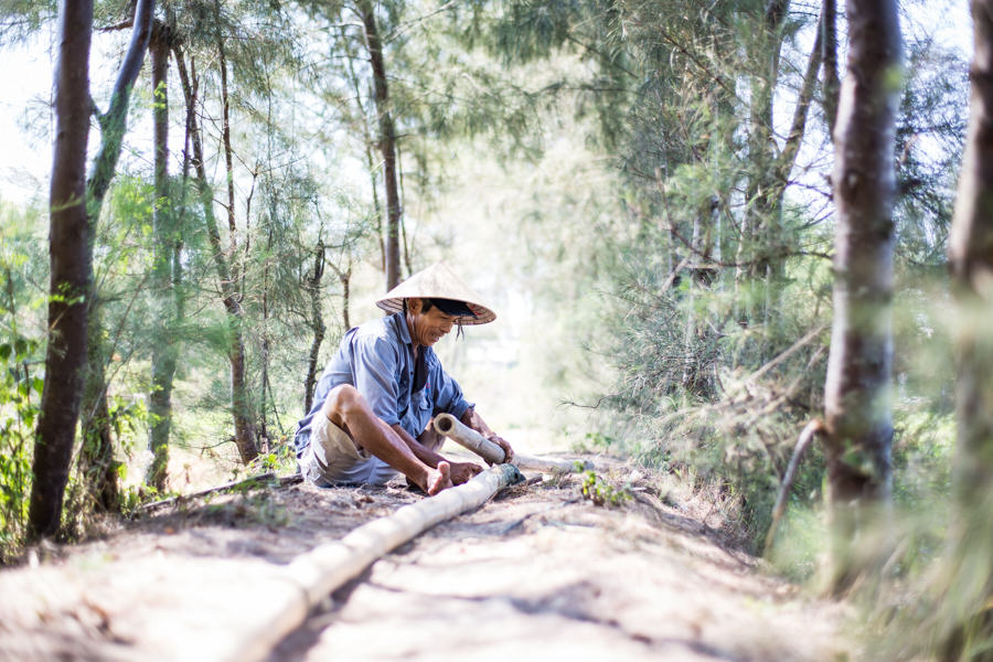 Vietnamese man cutting wood