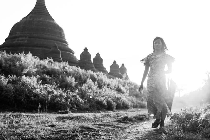 Myanmar girl walking with temple of Mrauk U