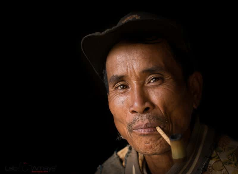 Portrait of a Lao man smoking a pipe