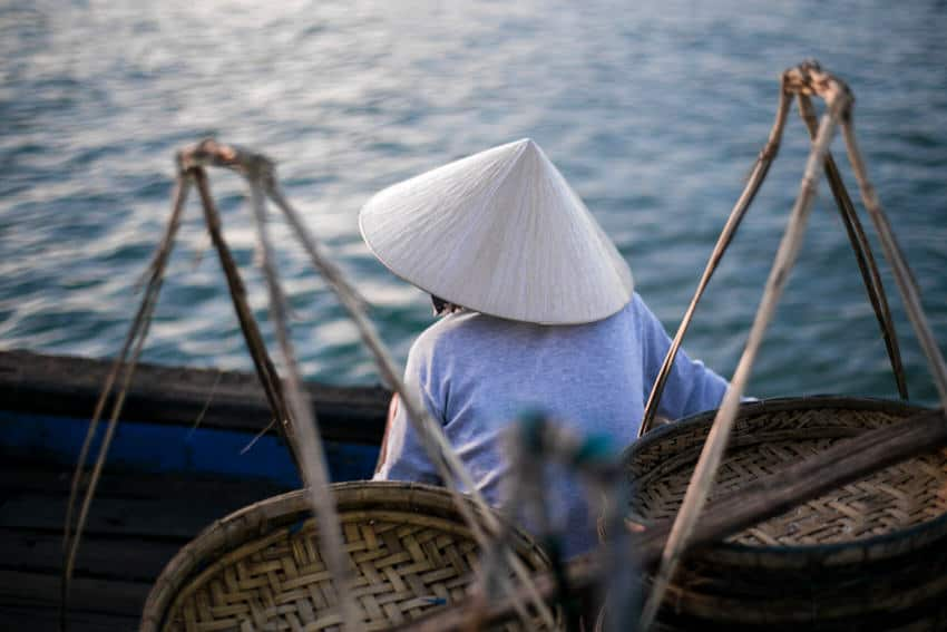 Vietnamese woman on a boat at sunrise