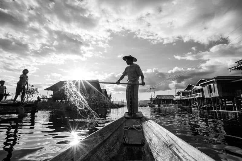 A man throws water on kids on Inle lake in Myanmar