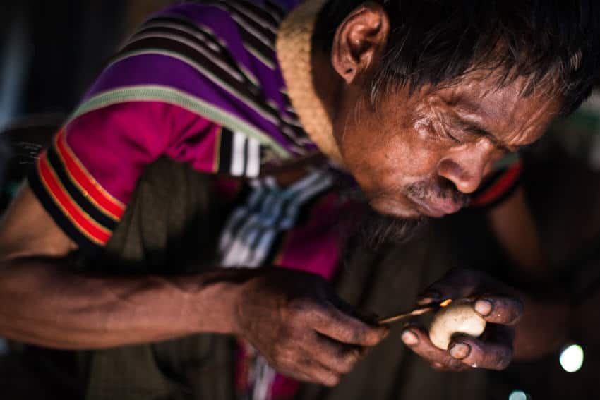 Shaman blowing on fire to burn an egg shell