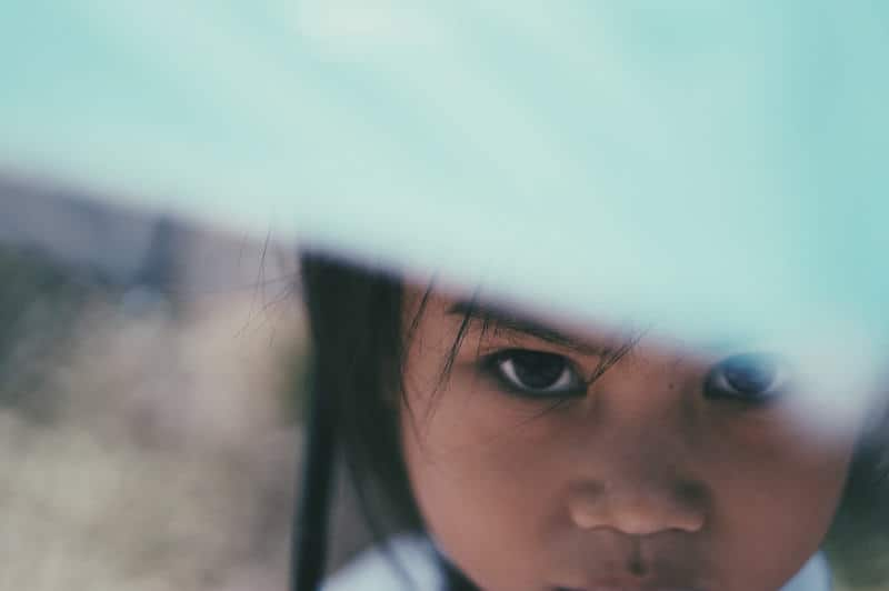 portrait of a young Lao girl hiding