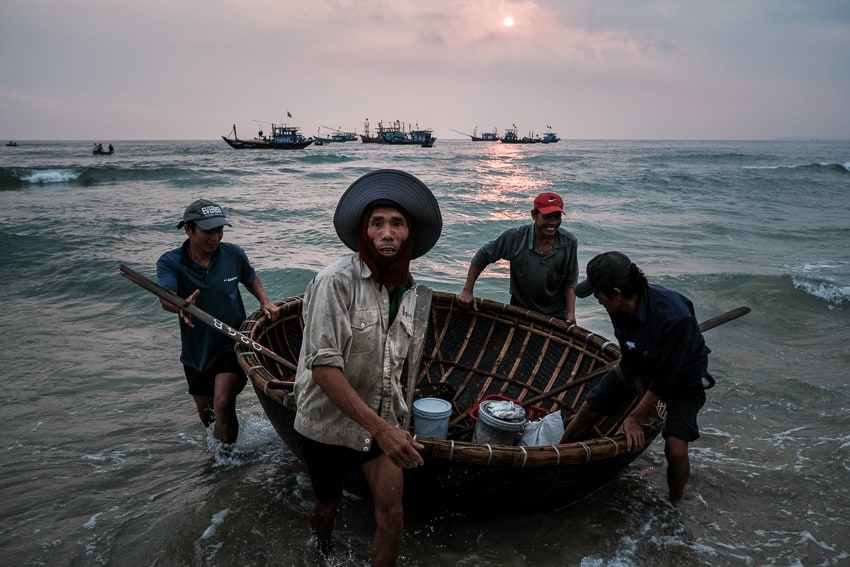 A group of fishermen push their boat into the waves as they come back from a night at sea in a fishing village near Hoi An, Vietnam