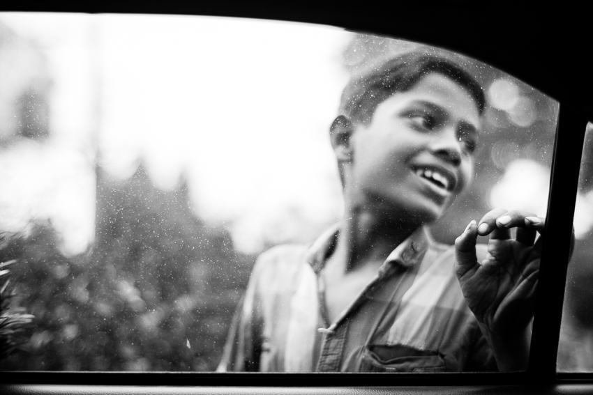 Young boy in Bangladesh selling papers to car drivers