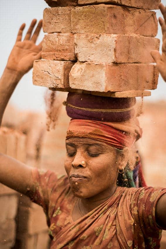 Bangladesh woman carrying bricks on her head