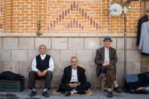 3 men sitting in the street in Iran