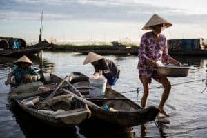Three Vietnamese women are carrying their catch from the boat to shore