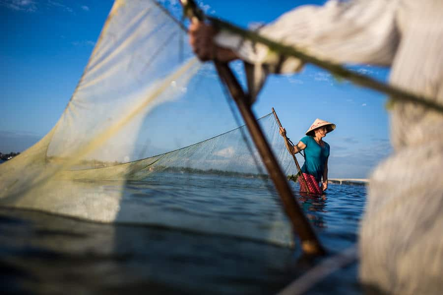 A large net is dragged through the water by a pair of fishermen in Vietnam