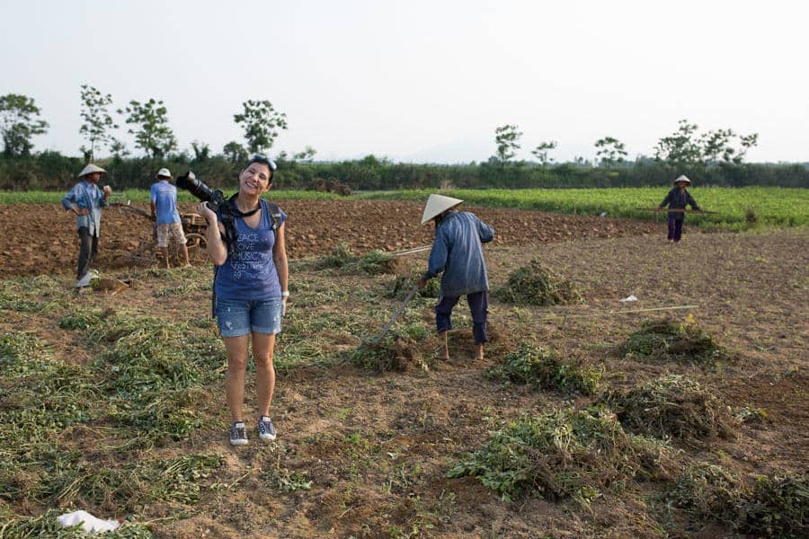 A photography student standing in a field with farmers in Vietnam on a photo tour with Pics of Asia