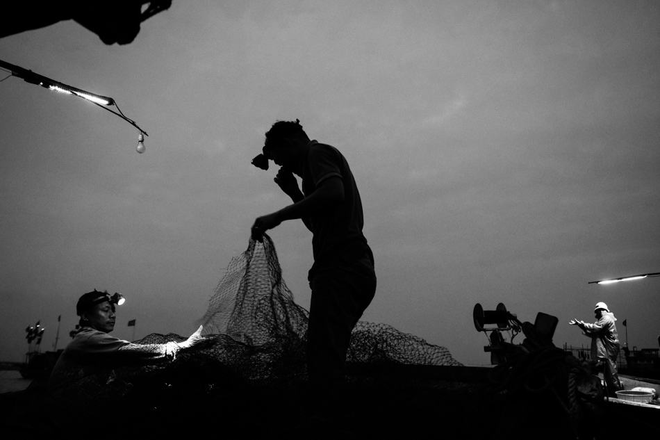 A fisherman's silhouette is seen holding up a net at night with head torch lit