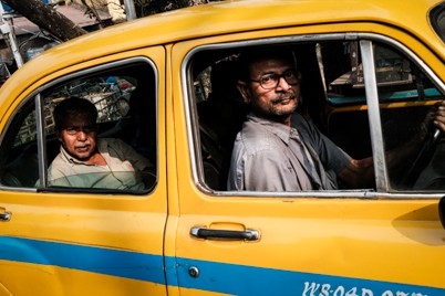 A taxi driver and passenger in a signature yellow taxi in Kolkata during a photography tour by Pics of Asia