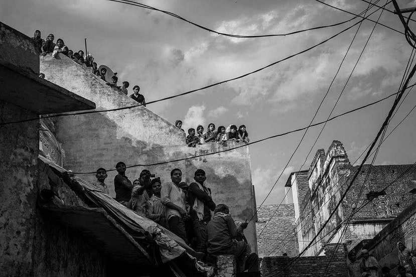 A crowd of onlookers sit on the rooftops in Varanasi India - Pics of Asia on Location