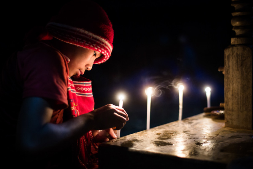 A young man in a red hat lights a prayer candle in a temple in Myanmar - Taken On Tour With Pics Of Asia
