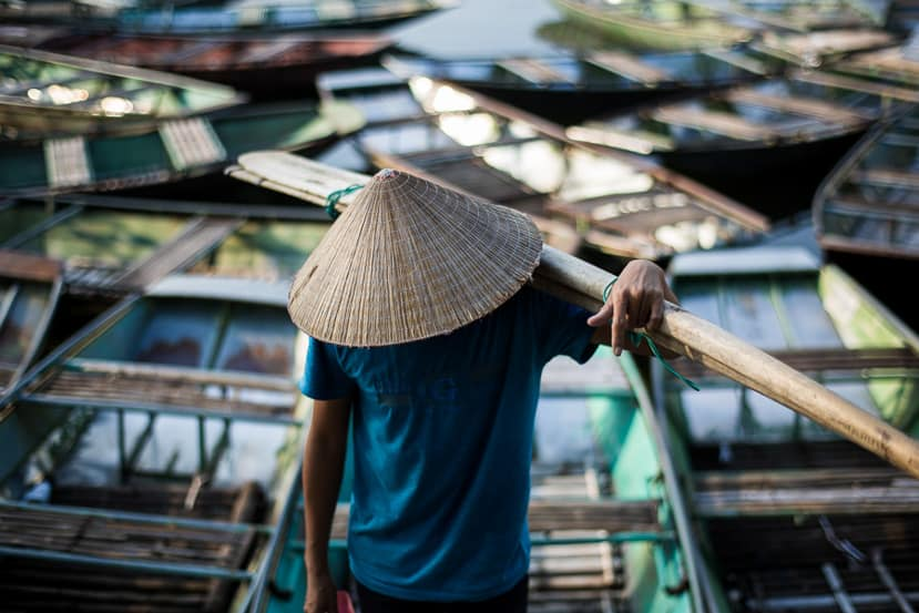 A farmer in rice paper hat hauls his oars amon a river of boats in Nam Dinh Vietnam - Pics Of Asia Photos Travels Tours
