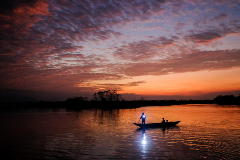A single long boat moves down the river as the sun sets in cental Vietnam's Mekong Delta - Pics of Asia Travel Photography Tours