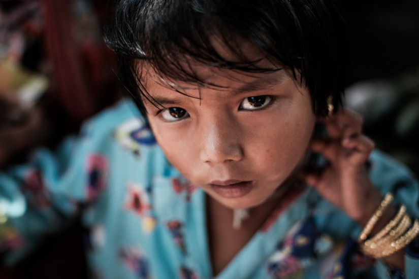 An up close portrait of a young girl who looks up a camera in Myanmar - Taken On Tour With Pics Of Asia