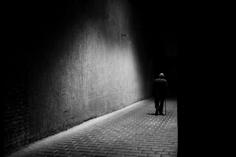 A black and white photo of an old man with a cane walking down a dark brick alley in Iran - Pics Of Asia Phototours