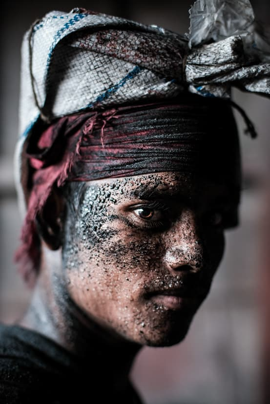portrait of a man unloading coal from boats in Dhaka