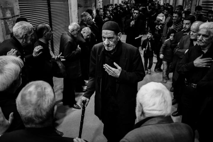 An old man walks though a crowd with hand on heart in Iran - Pics of Asia Photography Tours