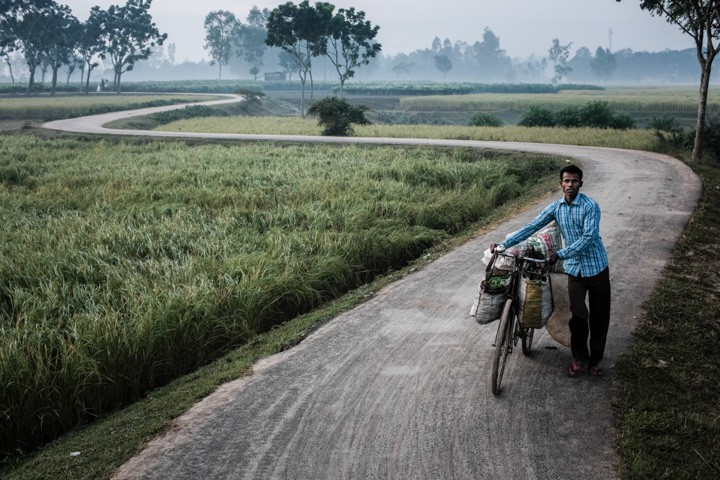Man pushing his bicycle in the countryside of Dinajpur