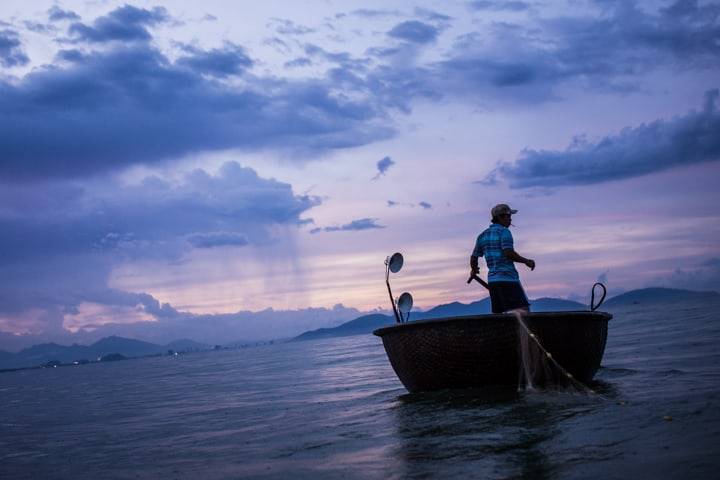 A Fishman In A Basket Boat Trails His Fishing Nets At Sunset - Taken On Tour With Pics Of Asia
