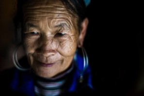 An Up-close portrait of a Hmong woman on a black background in North Vietnam - Pics Of Asia Photos Travels Tours