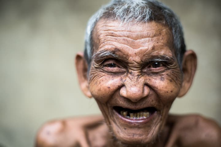 An elderly man laughs and smiles at camera in Myanmar - Pics Of Asia Phototours