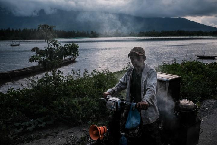 man in Vietnam selling banh bao on his smoking motorbike in front of Lang Co lagoon