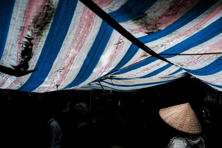 Market Tarps In Red White And Blue Cast A Haunting Light On A Girl In A Rice Paper Hat, Ninh Binh Market - Pics Of Asia Photos Travels Tours