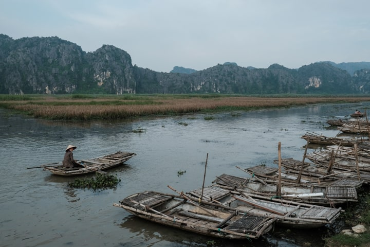 Bamboo boats and a lime stone mountain background in Vietnam's Ninh Binh - Pics Of Asia Photos Travels Tours