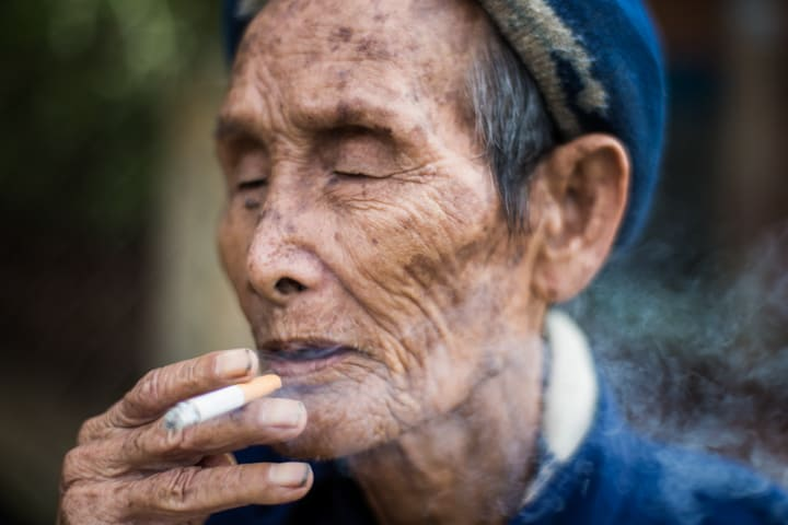 An old man in blue enjoys a long inhale on a cigarette in Central Vietnam - Pics Of Asia Photo Workshop Tours