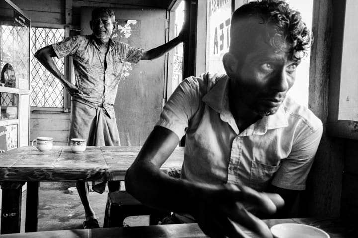 A young man reaches for his tea in a local Sri Lanka tea shop - Pics Of Asia Black And White Photography